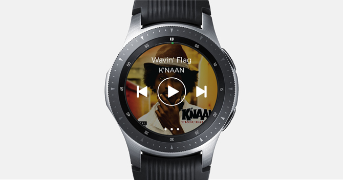 Screenshot of the Galaxy Watch with Spotify app with music controls and album cover in the background.